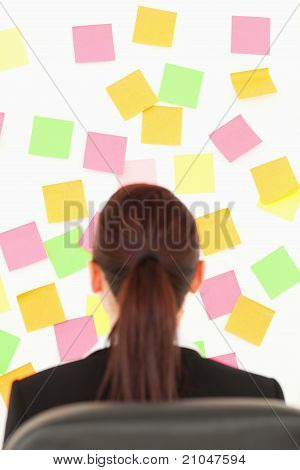 Redhead Woman Looking At A Wall Full Of Repositional Notes