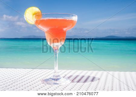 Strawberry Daiquiri cocktail on the white rattan table at the beach restaurant with beautiful blue sea and sky background