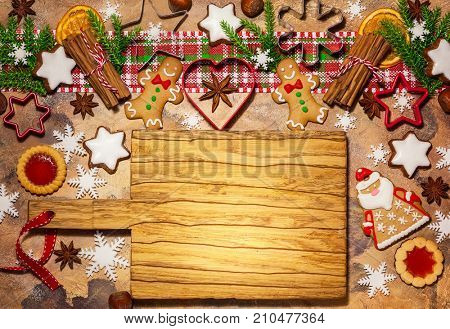 Christmas baking background with assorted Christmas cookies, spices, cookie molds and wooden cutting board. Top view.