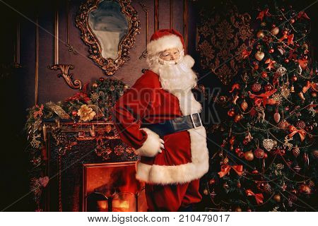Santa Claus next to a beautiful ornate Christmas tree. Santa Claus dress up the Christmas tree. Retro style.