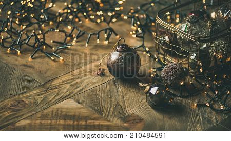 Christmas or New Year background, preparing for holiday. Christmas tree toy decoration balls in vintage box and light garland over rustic wooden background, selective focus, copy space