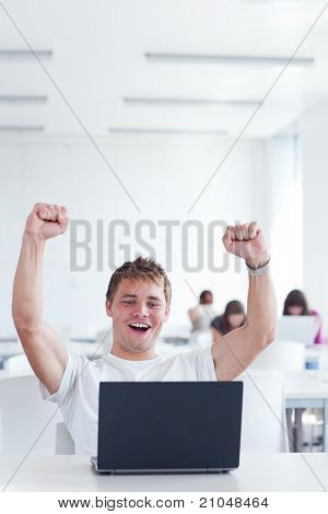 Yes! - happy young male college student, rejoicing over his success while working on his laptop computer in a study room (color toned image)