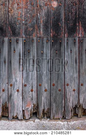 Detail of old and textured wooden door with rusty nails in an abandoned house