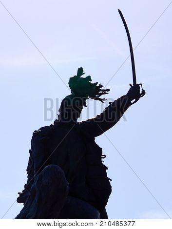 Statue of old Roman soldier with raised bayonet ready for war