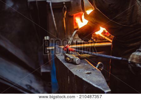 Blacksmith working on metal on anvil at forge high speed detail shot