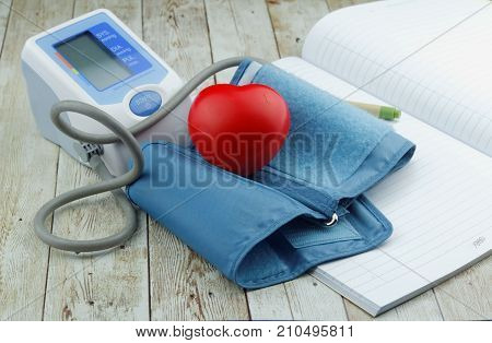 Blood pressure meter heart shape symbol and blank note book on wooden background.