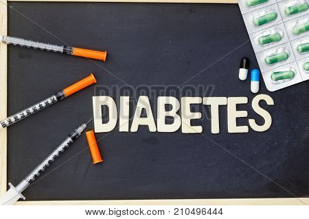 Word DIABETES with insulin syringe and medication on blackboard