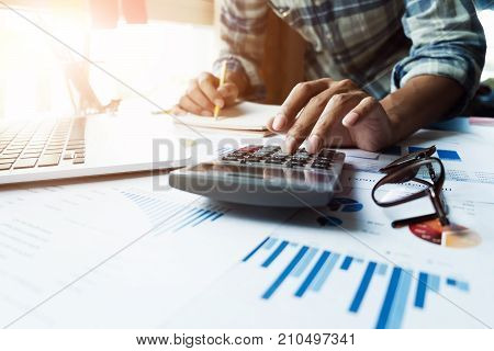 Close Up Of Businessman Or Accountant Hand Holding Pen Working On Calculator And Laptop Computer To