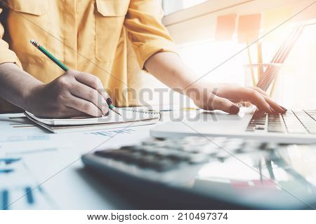 A Woman Using Laptop Computer To Analysis Data Report During Writing Make Note Some Data On Notepad,