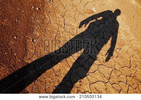 Shadow of man over cracked drought land, result of global warming
