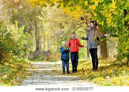 Mom And Her Sons Toss The Leaves. Autumn Park.