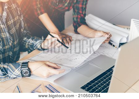 Two Engineering Man Or Co-workers Working On A Project And Discussing Together With Looking At Bluep