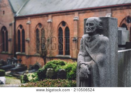 December, 29th, 2016 - Ghent, East Flanders, Belgium. Stone cemetery statue of a man and brick church on Campo Santo historical old graveyard in Sint-amandsberg municipality, Gent.