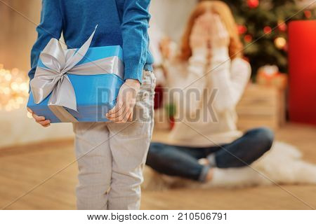 Adorable moment. Close up on a kid wearing casual attire holding a beautifully wrapped gift behind his back while surprising his mother on a Christmas morning.