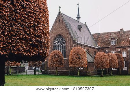 Ghent, Belgium - December 29th, 2016. Autumn park and church in New Saint Elisabeth beguinage in Sint-Amandsberg district, Gent. Known as Groot Begijnhof Sint-Amandsberg. Flanders World Heritage Site.