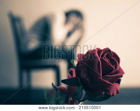 Retro sad woman sitting and crying with red rose in focus. Lonly love emotion concept.