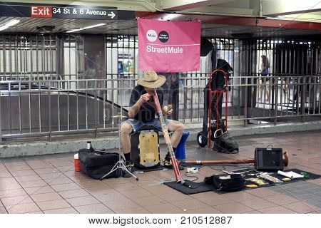 NEW YORK NEW YORK USA - AUGUST 6: Subway performer blows into a didgeridoo. Taken August 6 2017 in New York.