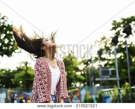 Young woman flinging her hair at an amusement park