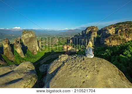 Woman traveler resting at Meteora landscape resting at Meteora overlook in Thessaly, Greece. Female hiker sitting on a rock on oper air. Best view point Psaropetra. Tourism in Europe.