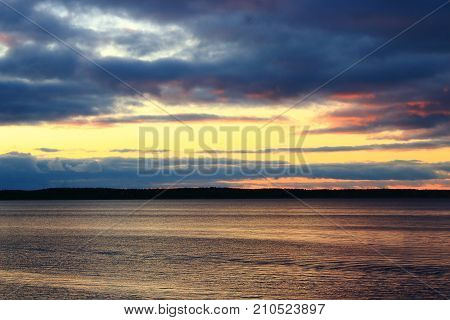 Beautiful sunset nature. Sunset on the lake. Evening landscape. Clouds over the lake. The horizon at sunset. Sea, lake at sunset. The waves on the river. The lake in Russia