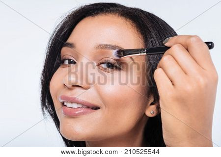 Love makeup. The close up of a beautiful young woman with a swarthy complexion applying eyeshadows and smiling at the camera while standing on a white background