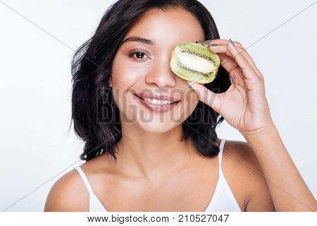 Source of vitamins. Beautiful young woman with a swarthy complexion holding a kiwifruit near her eye while posing against a white background