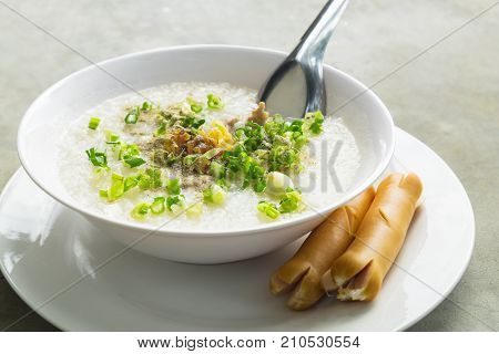 Pork Rice Porridge Congee Morning Breakfast on the concrete table serving with Sausage.