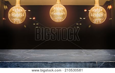 Black stone marble table top on blurred of counter cafe and coffee shop interior background with lighting vintage old lamp - can used for display or montage your products.