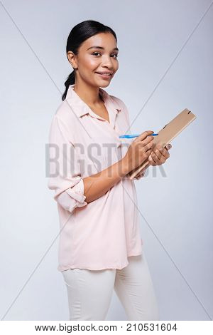 I love order. Pleasant young woman with a swarthy complexion being about to sign her folder with a blue marker pen while standing against a blue background