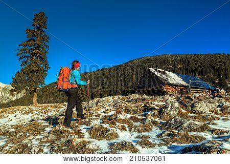Stunning winter landscape and young tourist woman with colorful backpack, Piatra Craiului mountains, Carpathians, Transylvania, Romania, Europe