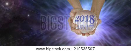 Ask a fortune teller for a 2018 reading -  pair of hands holding a large crystal ball showing 2018 fading out 2017 on a deep space background with a burst of energy behind