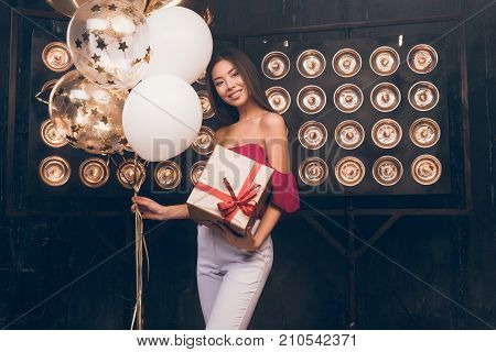 Asian girl with balloons and box of gift smiling and happy, celebrate New Year party! Wish you a Merry Christmas! Girl with a Christmas presents. Happy feeling to New Year. Christmas party 2018