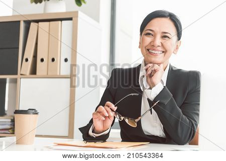 Portrait of pensive career woman with beautiful smile situating at desk in apartment. Job concept