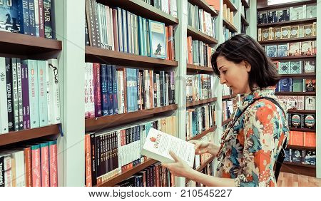 Eskisehir Turkey - August 11 2017: Young brunette woman looking for a book in a retail bookstore chain in Eskisehir Turkey.