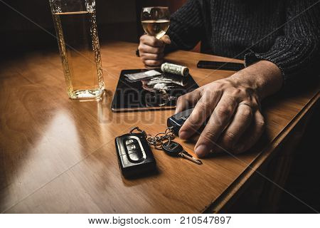 Man takes car keys after using cocaine drug and drinking whiskey. Drugs and alcohol, danger drunk driving concept