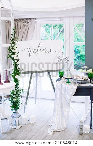 Wedding decorations with flowers in Boho style with macarons on a table with large number od various decorations. Large windows on background. DIY