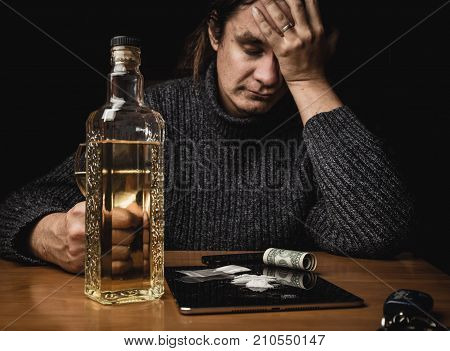 Man after sniffling cocaine drugs and drinking alcohol seats at the table and holding his head by hand. Drug abuse and loneliness alcoholism concept