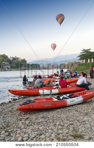 Vang Vieng, Laos - November 2015: Hot Air Balloons Flying Over Nam Song River And Tourist Kayaks In