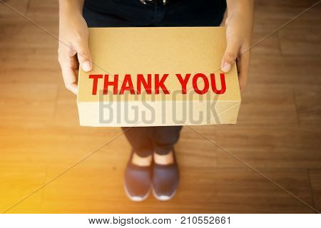Thank you message for customer who shopping with your shop concept : Thank you message word on simple delivery brown box in hand of friendly sender man