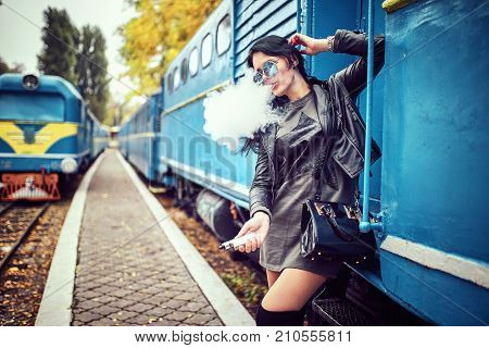 Elegant woman smoking e-cigarette with smoke wearing suit and hat