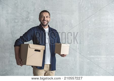 Delivery service concept. Portrait of joyful upbeat bearded deliveryman who is holding parcels and expressing positivity while standing against gray wall background. Copy space in the right side