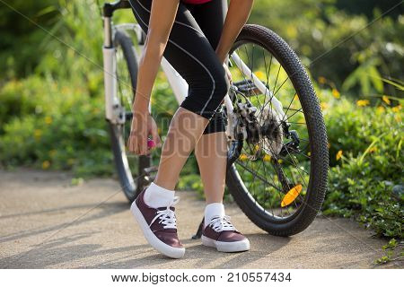 Woman spraying mosquito repellent on skin before cycling in nature