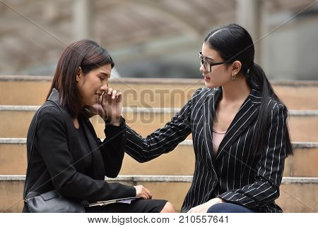 Young Asian Business woman comforting her friend. Sadness Female crying and sitting on the stair. Sacked.