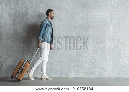 Outward journey. Full length profile of cute bearded traveler who is pulling his suitcase. Gray wall in background. Copy space in the right side