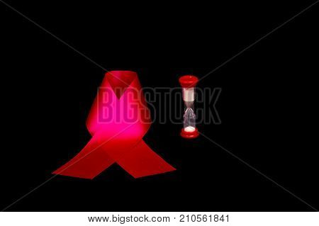 Red aids ribbon on isolation and next an hourglass. Time goes memory remains. AIDS HIV CANCER. World AIDS Day. Black background