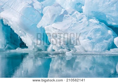 Blue growler piece of iceberg with reflection in calm water. Global warming, melting of ice. Arctic ocean