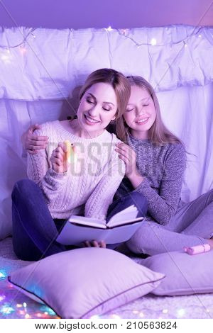 Enjoying reading. Alive young loving mother and daughter hugging and mom holding a torch while reading a book