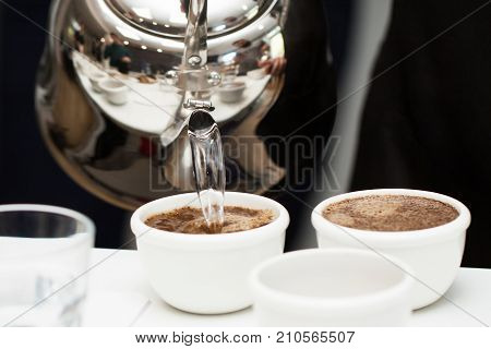 Brewing coffee with boiling water from a metal kettle in white cups. Subject of professional preparation of coffee, barista's secrets, invigorating fresh coffee, etc.