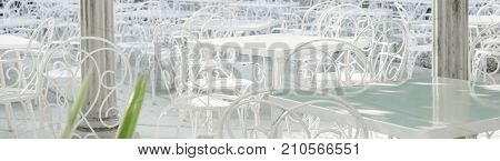 white tables and chairs in a cafe on the street outdoor