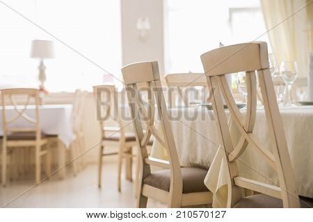 Elegant served table with wine glasses and white wooden chairs in modern restaurant